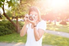 Het leuke meisje op zonnige dag in parkeren die foto's met analogon nemen kwam stock fotografie