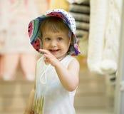 Het leuke meisje probeert op kleurrijke hoed in kinderenopslag Royalty-vrije Stock Foto's