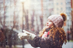 Het leuke meisje rekt haar hand uit om dalende sneeuwvlokken te vangen royalty-vrije stock foto