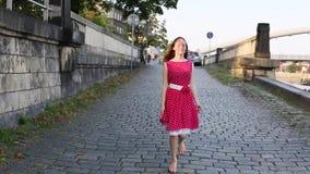 Het leuke meisje in rode kleding stelt het overslaan op de bestrating in werking stock footage