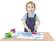 Het leuke meisje schilderen op klein bureau die aan camera kijken royalty-vrije stock afbeelding