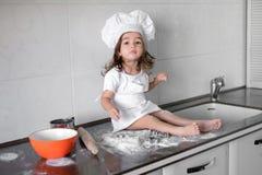 Het leuke meisje in schort en chef-kokhoed kneedt het deeg en glimlacht terwijl het bakken Stock Afbeeldingen