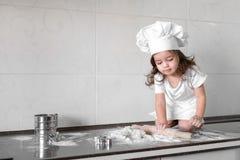 Het leuke meisje in schort en chef-kokhoed kneedt het deeg en glimlacht terwijl het bakken Stock Foto