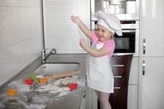 Het leuke meisje in schort en chef-kokhoed kneedt het deeg en glimlacht terwijl het bakken Stock Afbeelding