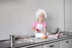 Het leuke meisje in schort en chef-kokhoed kneedt het deeg en glimlacht terwijl het bakken Royalty-vrije Stock Afbeelding