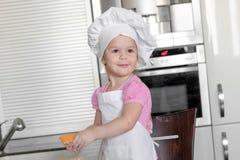 Het leuke meisje in schort en chef-kokhoed kneedt het deeg en glimlacht terwijl het bakken Royalty-vrije Stock Foto's