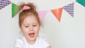 Het leuke meisje slaat haar handen, verheugt zich, applaus Portret van een grappig kind dat close-up toejuicht stock video