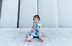Het leuke meisje smilling dichtbij de grijze muur Kinderjarenconcept royalty-vrije stock fotografie
