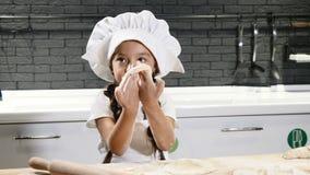 Het leuke meisje spelen in binnenlandse keuken Deeg, bloem en deegrol op lijst De kinderen handelen als volwassenen grappig stock videobeelden
