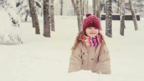 Het leuke meisje spelen in de sneeuw, werpt omhoog sneeuwvlokken stock footage