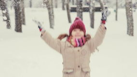 Het leuke meisje spelen in de sneeuw, werpt omhoog sneeuwvlokken stock video