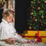 Het leuke meisje spelen dichtbij open haard en verfraaide Kerstboom Stock Fotografie
