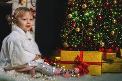 Het leuke meisje spelen dichtbij open haard en verfraaide Kerstboom Royalty-vrije Stock Foto's