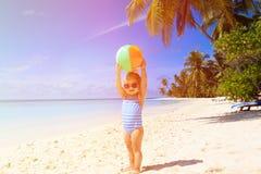 Het leuke meisje spelen met bal op het strand Stock Foto's