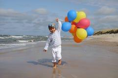 Het leuke meisje spelen met ballons op het strand Stock Afbeelding