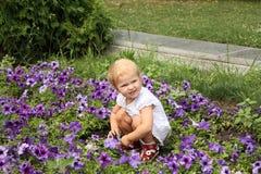 Het leuke meisje spelen met bloemen Stock Afbeeldingen