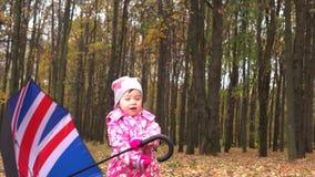 Het leuke meisje spelen met Britse vlag-als paraplu in de herfstpark Slecht weerconcept 4K steadicam schot stock videobeelden