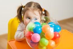 Het leuke meisje spelen met gekleurde ballen stock afbeeldingen