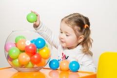 Het leuke meisje spelen met gekleurde ballen stock fotografie