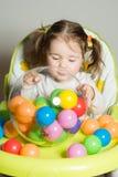 Het leuke meisje spelen met gekleurde ballen royalty-vrije stock fotografie
