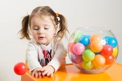 Het leuke meisje spelen met gekleurde ballen stock foto's