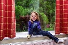 Het leuke meisje spelen met gordijn op het venster stock afbeeldingen