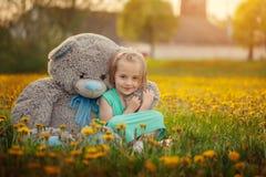 Het leuke meisje spelen met grote beer in de zomer royalty-vrije stock foto's