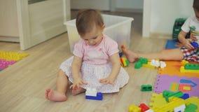 Het leuke meisje spelen met kleurrijke blokken stock video