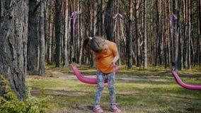 Het leuke meisje spelen met kleurrijke schommeling in het bos stock video