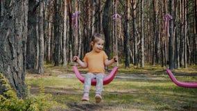 Het leuke meisje spelen met kleurrijke schommeling in het bos stock footage