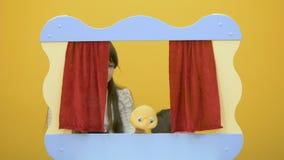 Het leuke meisje spelen met stuk speelgoed achter het scherm van poppenspel stock video