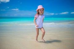 Het leuke meisje spelen in ondiep water bij royalty-vrije stock afbeeldingen