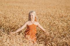 Het leuke meisje spelen op het de zomergebied van tarwe Royalty-vrije Stock Afbeeldingen