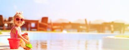 Het leuke meisje spelen in zwembad bij strand stock afbeelding