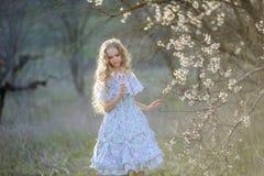 Het leuke meisje van het blondehaar in een lange gekronkelde kleding, die in bloeiende fruittuin lopen stock afbeelding