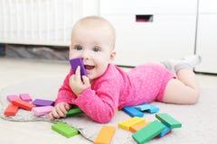 Het leuke meisje van de 6 maandbaby speelt thuis houten multicolored meccano Royalty-vrije Stock Foto