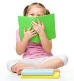 Het leuke meisje verbergt achter een boek Stock Foto