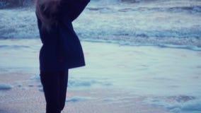 Het leuke meisje werpt schuim van golven en verheugt zich, lacht Overzees, golven, wind op achtergrond stock videobeelden