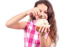 Het leuke meisje zet een muntstuk in een varken-piggy bank stock fotografie