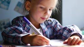 Het leuke Meisje zit bij Haar Lijst en trekt met Kleurpotloden stock videobeelden