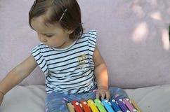 Het leuke het meisjespeuter van de kindbaby spelen met xylofoon thuis Creativiteit en onderwijsconcept vroege stert voor muziek royalty-vrije stock afbeelding