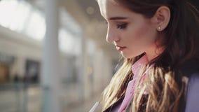 Het leuke mooie brunette in het roze overhemd en het zwarte sleeveless jasje is in het winkelcentrum Het meisje merkt op stock footage