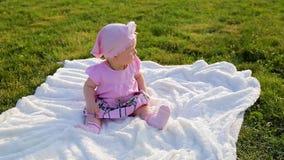 Het leuke mooie zuigelingsmeisje in roze kleren zit op witte die deken op groen gras in stadspark wordt gelegd stock videobeelden