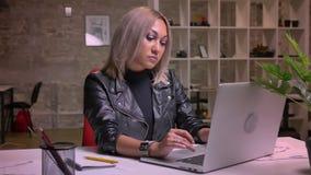 Het leuke nadenkende Kaukasische die blondewijfje typt op toetsenbord terwijl zitting op het haar werk wordt geïsoleerd binnen stock video