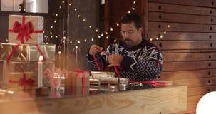 Het leuke paar in de wintersweaters die Kerstmis verpakken stelt voor stock videobeelden