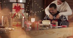 Het leuke paar in de wintersweaters die Kerstmis verpakken stelt voor stock footage