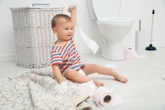 Het leuke peuter spelen met toiletpapier stock afbeelding