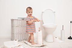 Het leuke peuter spelen met toiletpapier royalty-vrije stock afbeeldingen