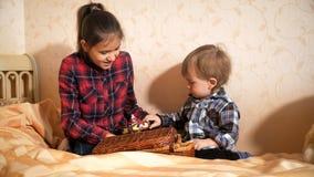Het leuke peuterjongen spelen met oudere zuster op bed bij slaapkamer stock fotografie