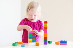 Het leuke peutermeisje plaing met kleurrijke blokken Stock Foto